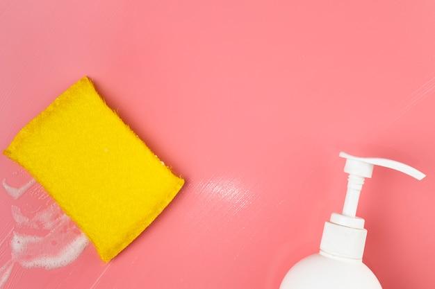 トップビューの白い石鹸のボトルとスポンジ