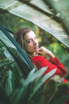 ぼやけた葉と赤いドレスを着た女性