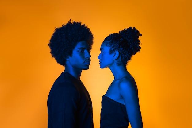 オレンジ色の背景と横向きのカップル