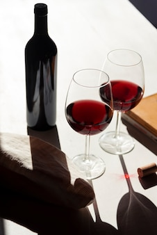 Красные бокалы вина рядом с бутылкой