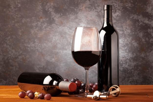 Бутылка красного вина с бокалом