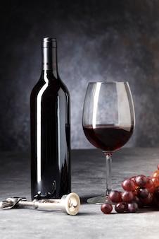 ワインの半分空のグラスの赤いボトル