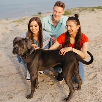 Полный выстрел счастливые друзья с милой собакой