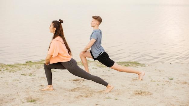 ビーチで運動するフルショットの人々