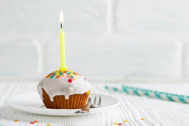 点灯ろうそくと艶をかけられたカップケーキ