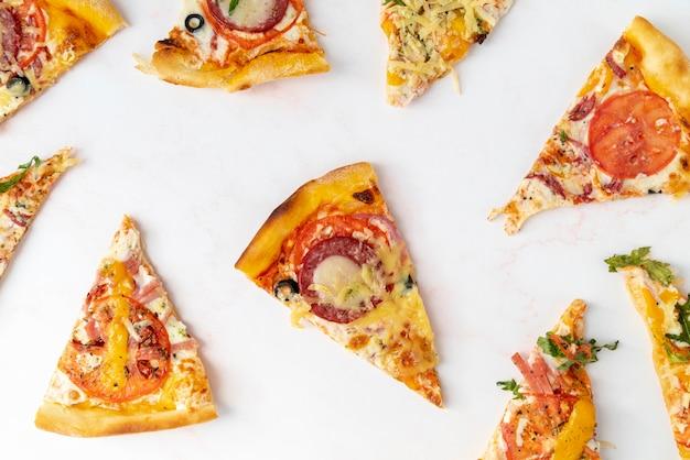 Вид сверху ломтики пиццы с белым фоном