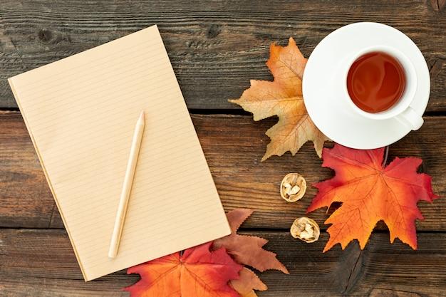 空のノートブックの横にコーヒーカップ