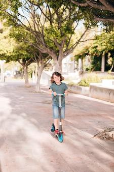 スクーターを持つ少年のロングショット
