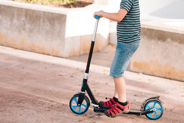 スクーターで少年のミディアムショット
