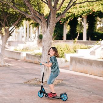 公園でスクーターを持つ少年のロングショット