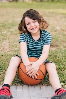 バスケットボールで草の中に座っている少年