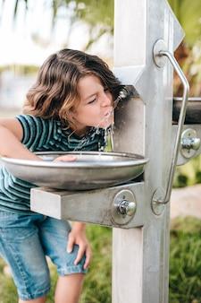 水を飲む少年の正面図
