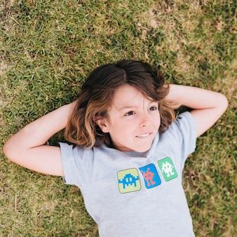 草の上に横たわる少年のミディアムショット
