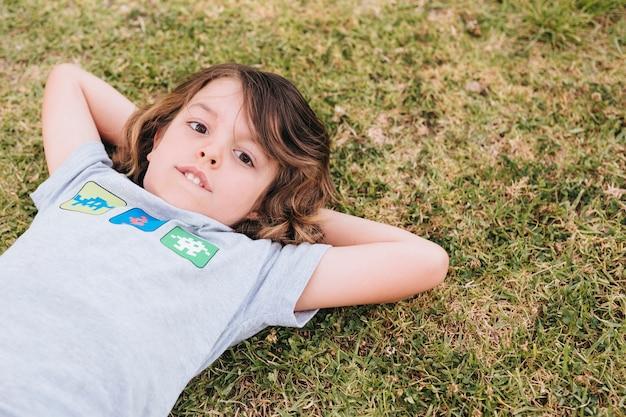 草の上に横たわる少年の正面図