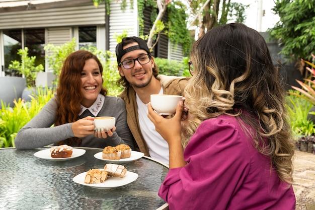 一緒にコーヒーを飲んでいる友人のミディアムショット