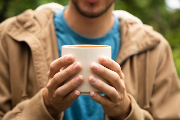 Крупный мужчина держит чашку кофе