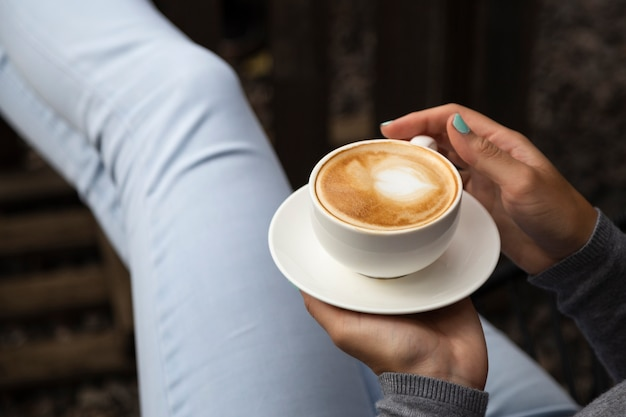 コーヒーカップとプレートを保持している女性のクローズアップ