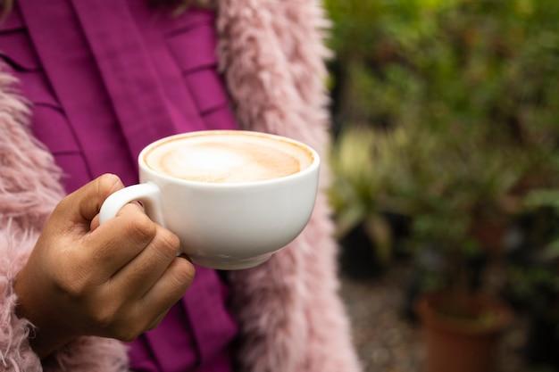一杯のコーヒーを保持している女性のクローズアップ