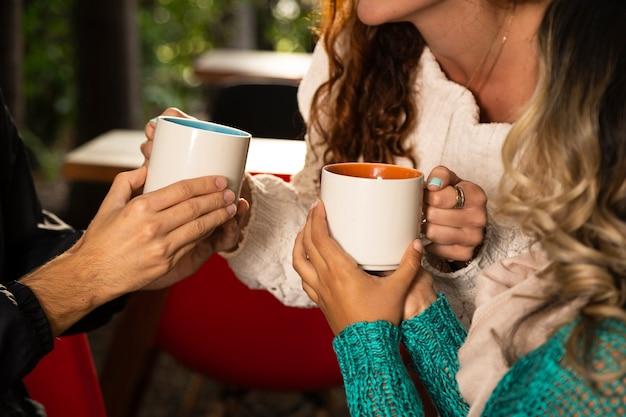 コーヒーカップを持つ友人のミディアムショット