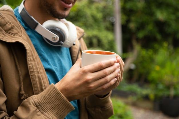 コーヒーマグを持って男の正面図
