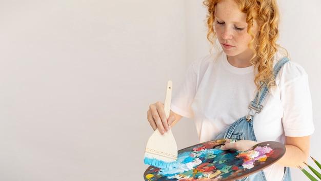 Вид сбоку девушка с предметами живописи