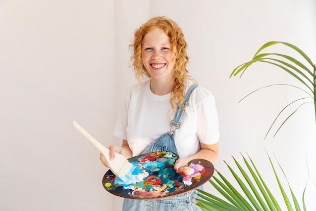 Средний снимок счастливая девушка держит палитру живописи