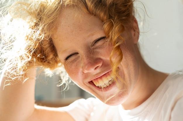 Крупным планом женщина с большой улыбкой и рыжими волосами