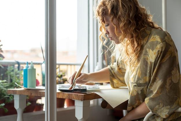 ミディアムショットの女性に座って、絵画