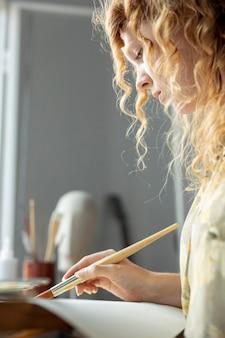 自宅で絵画のクローズアップの創造的な女性