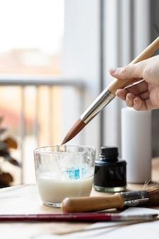 Рука крупным планом, используя стакан воды для рисования