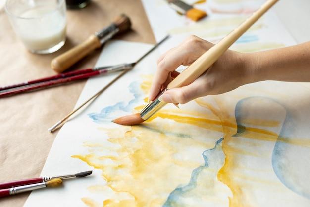 ブラシと絵画を保持しているクローズアップの女性