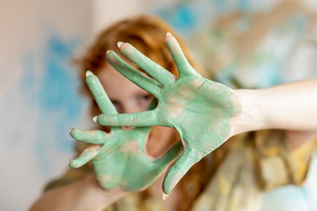 彼女の塗られた手のひらを示すクローズアップ女性