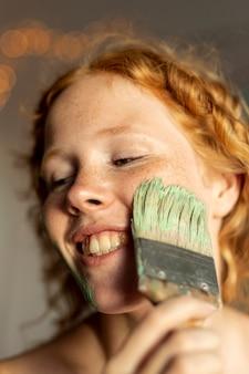 彼女の顔を塗るクローズアップ女性
