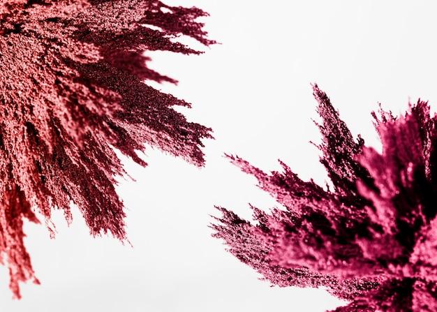 Розовая магнитная металлическая стружка на углу белого фона