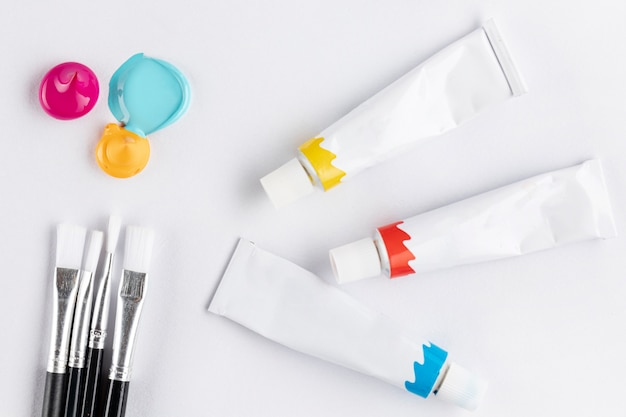 Кисти и краски трубы на белом столе