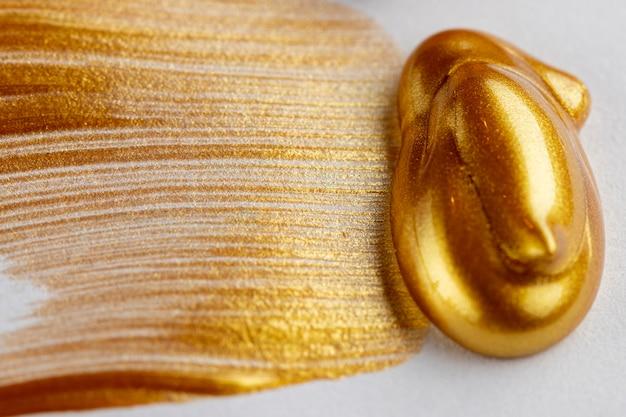 白い背景のキラキラの黄金塗料