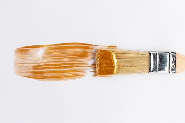 光沢のある黄金の塗料とブラシ