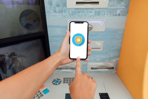 Крупный план смартфона рядом с банкоматом