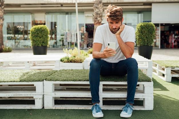 彼の携帯電話をチェックする退屈なひげを生やした男