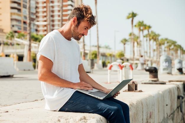 屋外のノートブックを保持している若い男