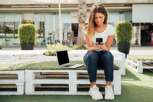 ポータブルデバイスで座っている若い女の子