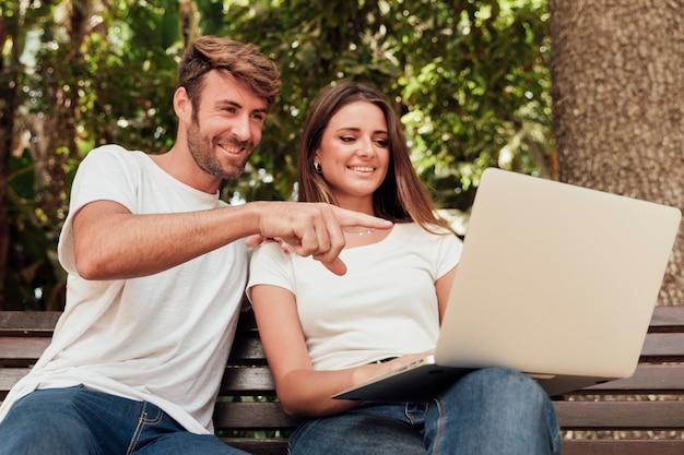 Милая пара на скамейке с ноутбуком