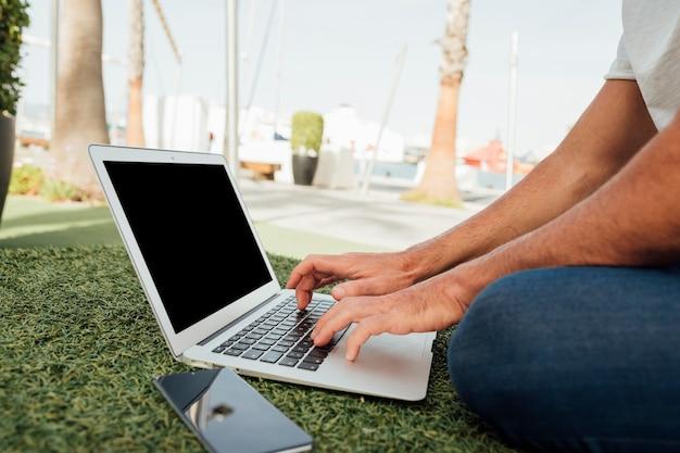 ポータブルデバイスで草の上に座っている男