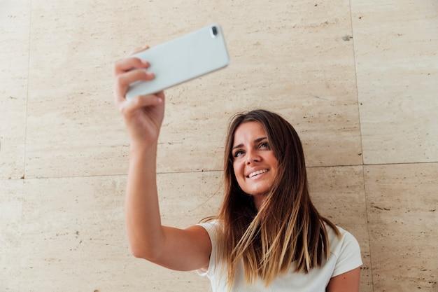 Счастливая девушка с телефоном, принимая селфи
