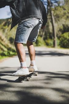 男のスケートボードの背面図