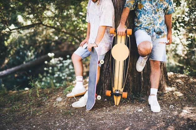 スケートボードを持つ友人のミディアムショット