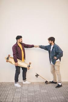 スケートボードを持つ友人の側面図