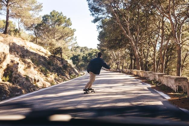 道路上のスケートボードを持つ男の背面図