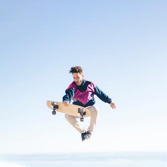 空気中のスケートボードを持つ男の正面図