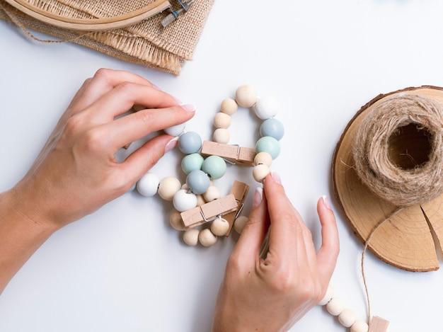 木製ビーズで装飾を作る女性